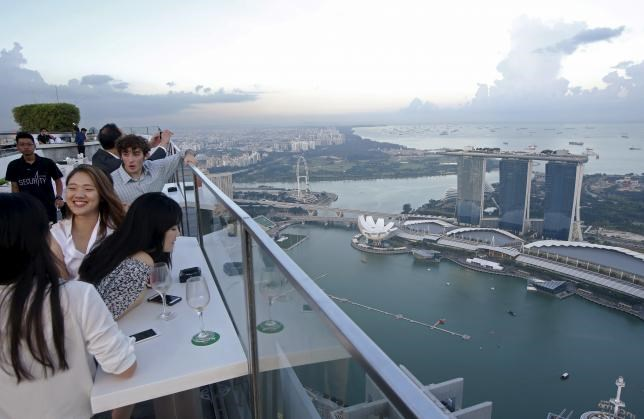 Vistors look out at the skyline from a rooftop bar in the central business district in Singapore July 24, 2015.