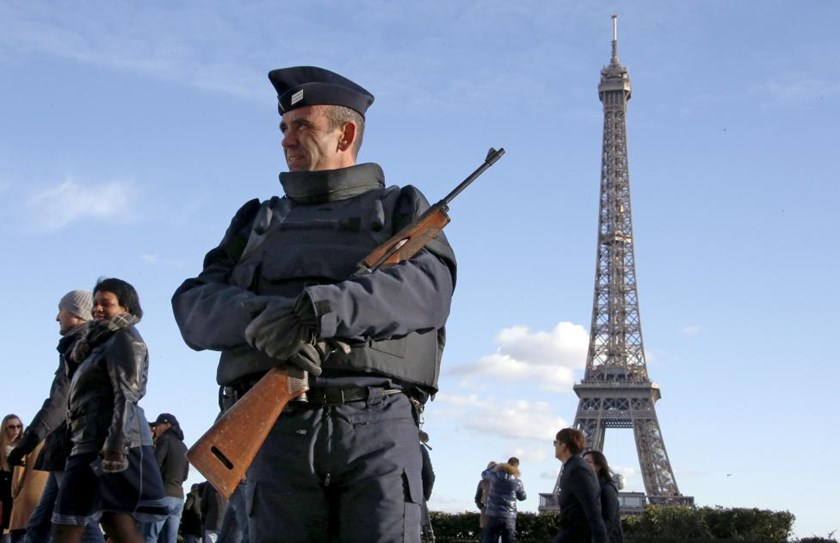 A French police officer stands guard by the Eiffel tower a week after a series of deadly attacks in the French capital Paris, France, November 22, 2015.