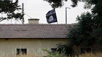 An Islamic State flag flies over the customs office of Syria's Jarablus border gate as it is pictured from the Turkish town of Karkamis.