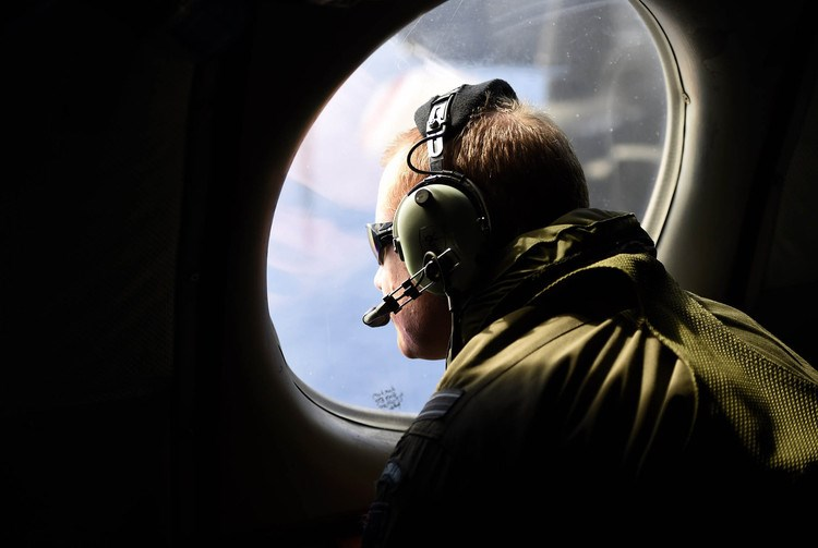 A crew member looks out an observation window aboard a Royal New Zealand Air Force maritime search aircraft. Photo: AFP