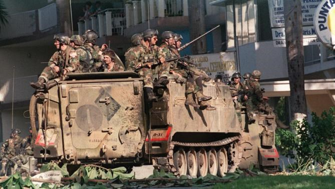 US soldiers atop armored vehicles take up a security position in a street of Panama City during Operation Just Cause, on December 23, 1989