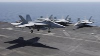 A F/A-18E/F Super Hornets of Strike Fighter Attack Squadron 211 (VFA-211) lands on the flight deck of the USS Theodore Roosevelt (CVN-71) aircraft carrier in the Gulf June 18, 2015.