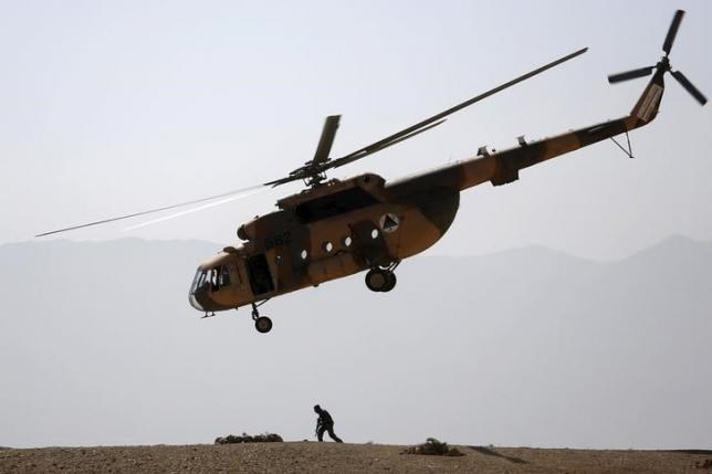 An Afghan National Army (ANA) helicopter flies over a soldier during a training exercise at the Kabul Military Training Centre in Afghanistan October 7, 2015.