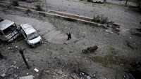 A man cleans up a damaged site after what activists said was shelling by forces loyal to Syria's President Bashar al-Assad in the Douma neighborhood of Damascus, Syria November 22, 2015.