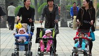 Women push babies in prams through a Beijing park