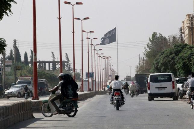Residents drive across a street with a fluttering Islamic State flag, in Tel Abyad town on the Syrian-Turkish border, Raqqa countryside September 24, 2014.