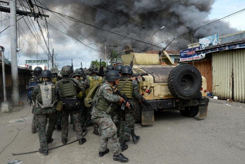 Members of the Philippine national police special forces take cover as they move toward enemy positions during a fire fight with Muslim rebels in Zamboanga City on September 12, 2013