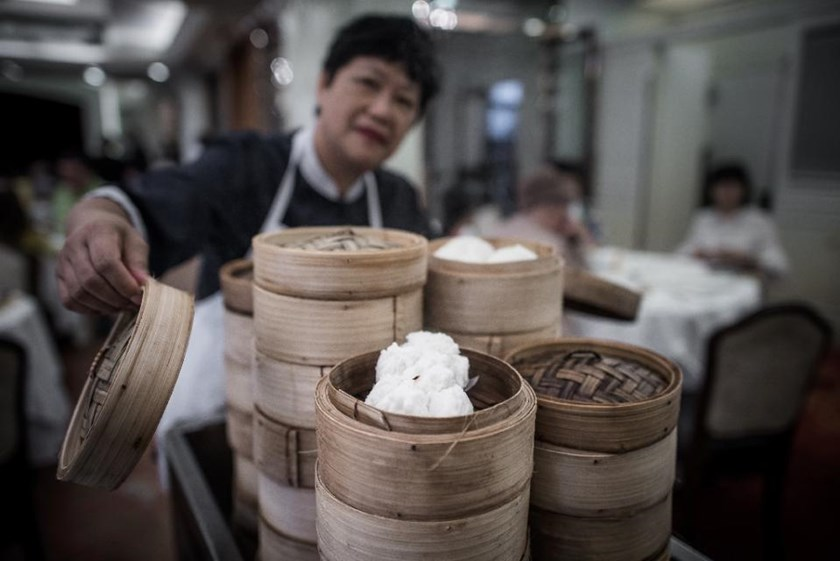 A waitress serves baskets of dim sum on a trolley in a restaurant in Hong Kong