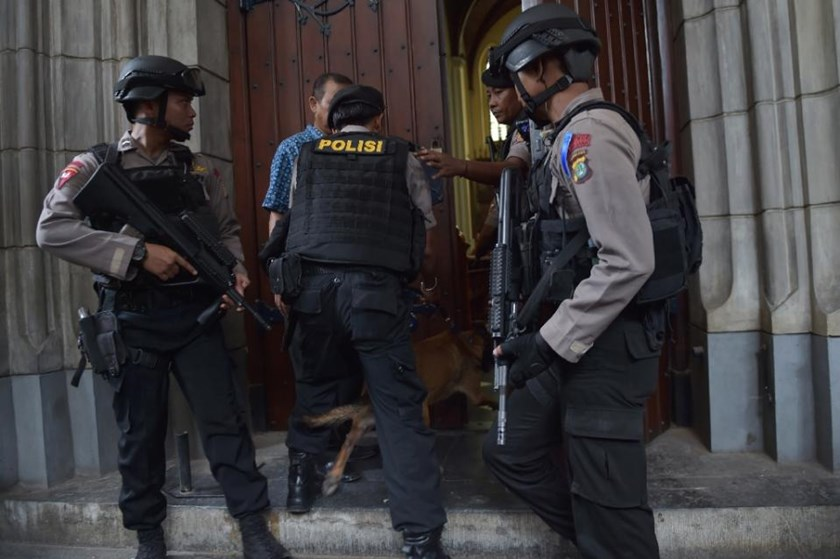 Indonesian anti-terror and bomb police enter a cathedral with a sniffer dog during a security check ahead of a mass service on Christmas eve in Jakarta on December 24, 2015