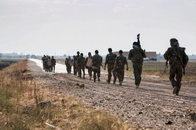 Kurdish fighters walk carrying their weapons towards Tel Abyad of Raqqa governorate after they said they took control of the area June 15, 2015.