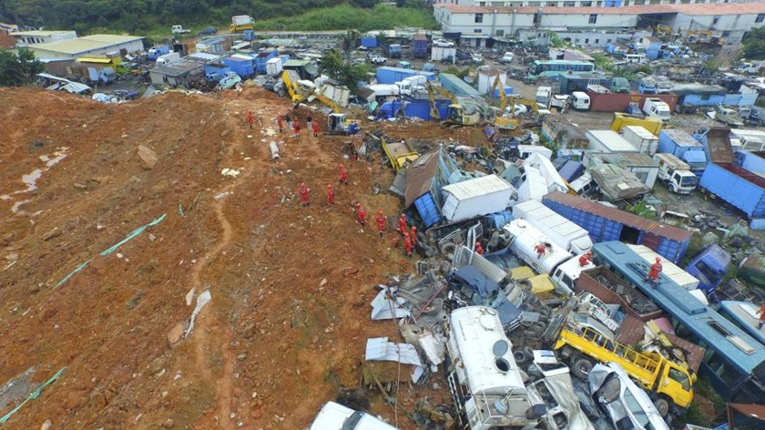 An aerial view shows rescuers walk among damaged vehicles to search for survivors at the site of a landslide which hit an industrial park on Sunday in Shenzhen, Guangdong province, China, December 22, 2015.