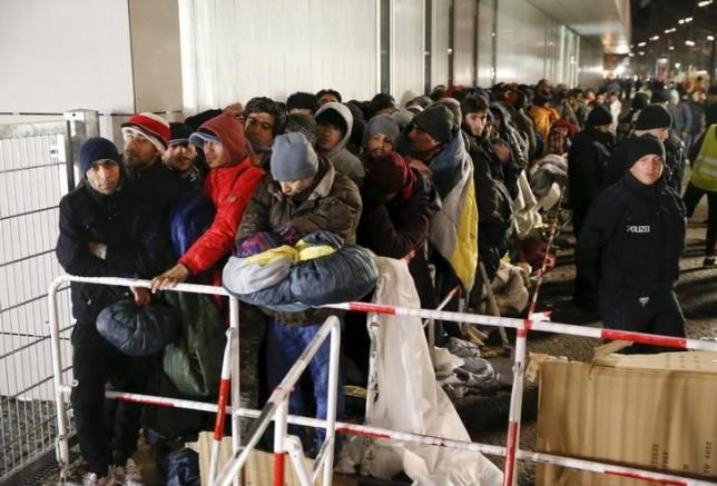 Migrants queue on a street to enter the compound outside the Berlin Office of Health and Social Affairs (LAGESO) for their registration process in Berlin, Germany, in this December 9, 2015 file picture.
