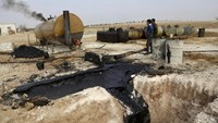 Men work at a makeshift oil refinery site in Marchmarin town, southern countryside of Idlib, Syria in this December 16, 2015, file photo.