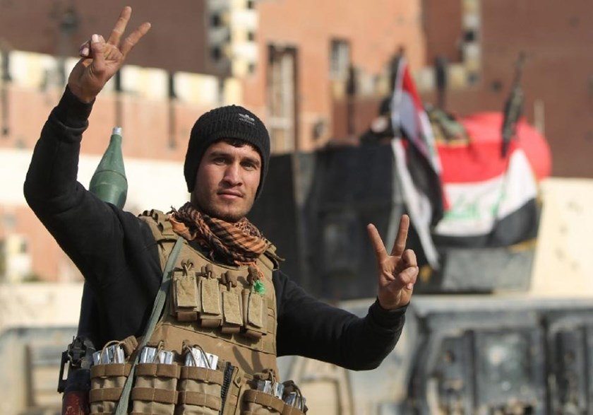 "A member of Iraq's elite counter-terrorism service flashes the ""V"" for victory sign on December 28, 2015 after Iraqi forces recaptured the city of Ramadi"