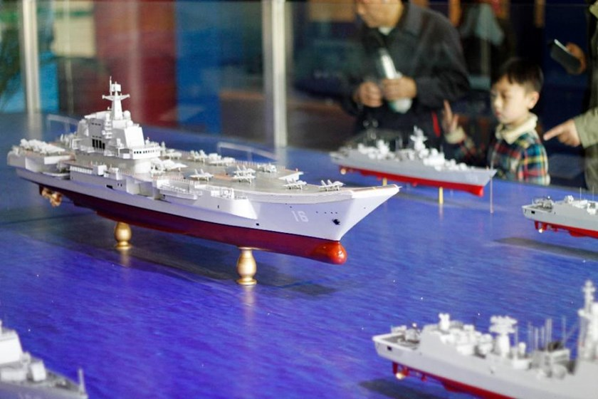 Visitors look at models of an aircraft carrier fleet, including China's first aircraft carrier Liaoning (C), on display at Defence Park in Nanjing, east China's Jiangsu province