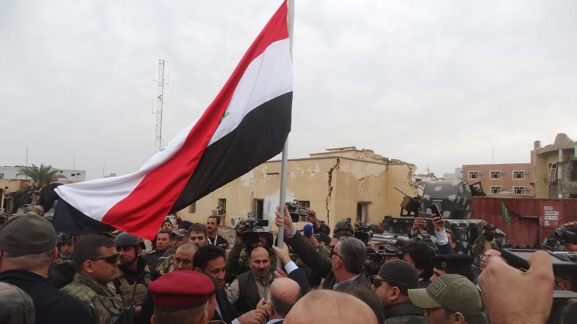 Iraqi Prime Minister Haider al-Abadi (C, back to camera) holds an Iraqi flag in the city of Ramadi, December 29, 2015.