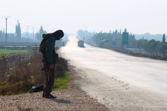 A fighter from a coalition of rebel groups called ''Jaish al Fateh'', also known as ''Army of Fatah'' (Conquest Army), secures a road as he waits for the passage of a convoy evacuating fighters and civilians from the two besieged Shi'ite towns of al-Foua and Kefraya in the mainly rebel-held northwestern province of Idlib, Syria December 28, 2015.