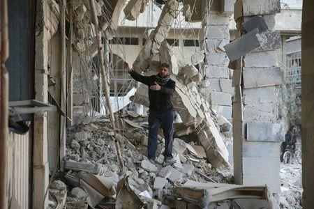 A man inspects a site damaged from what activists said was shelling by forces loyal to Assad in the town of Douma .