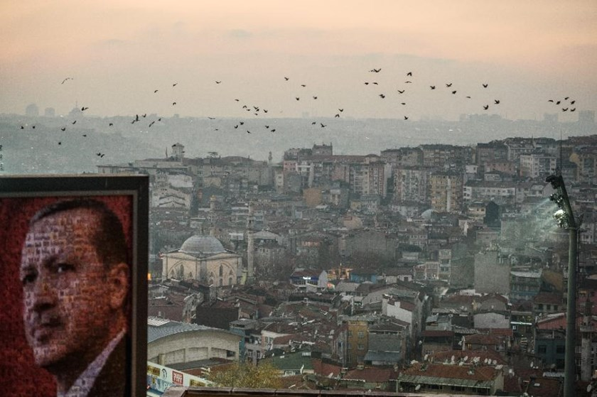 A poster of Turkish President Recep Tayyip Erdogan is seen over Kasimpasa district during a sunset on December 26, 2015 in Istanbul