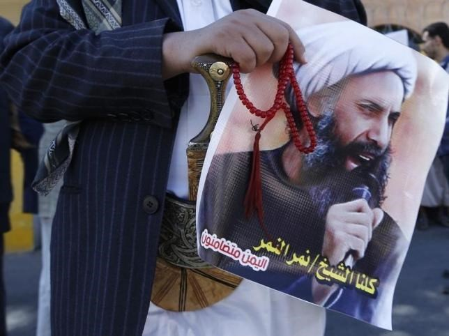 A Shi'ite protester carries a poster of Sheikh Nimr al-Nimr during a demonstration outside the Saudi embassy in Sanaa October 18, 2014.
