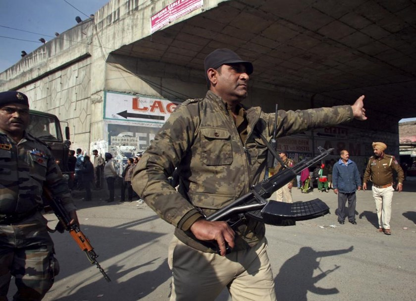 A security personnel asks people to move away from the area outside the Indian Air Force (IAF) base at Pathankot in Punjab, India, January 3, 2016.