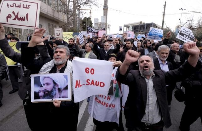 A protester holds a picture of Shi'ite cleric Sheikh Nimr al-Nimr, who was executed in Saudi Arabia, as others chant slogans during a rally after Friday prayers in Tehran January 8, 2016.