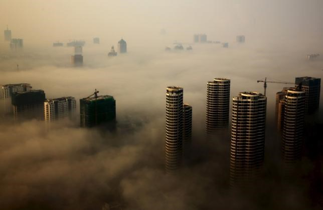 Buildings in construction are seen among mist during a hazy day in Rizhao, Shandong province, China, October 18, 2015.