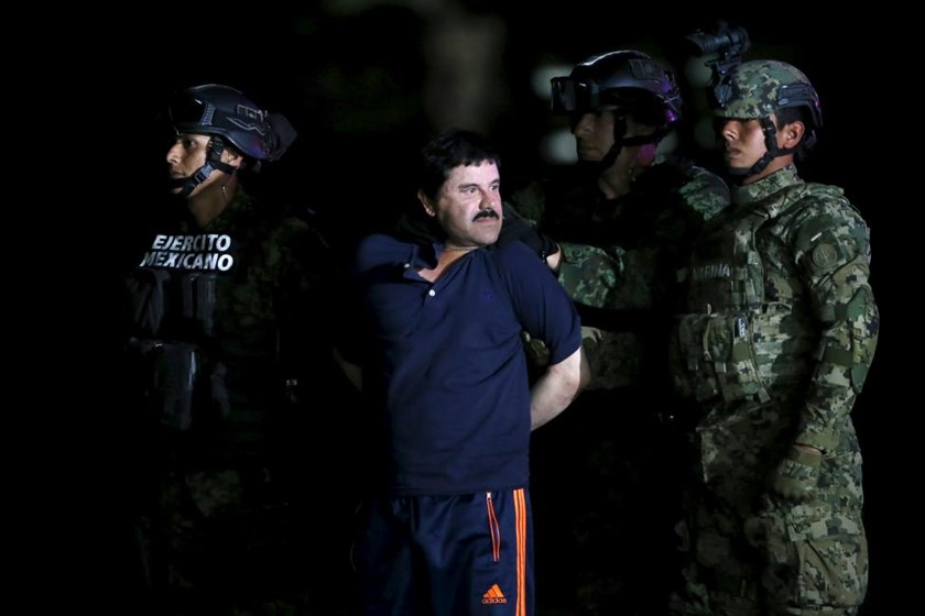 Joaquin 'El Chapo' Guzman is escorted by soldiers during a presentation at the hangar belonging to the office of the Attorney General in Mexico City, Mexico January 8, 2016.