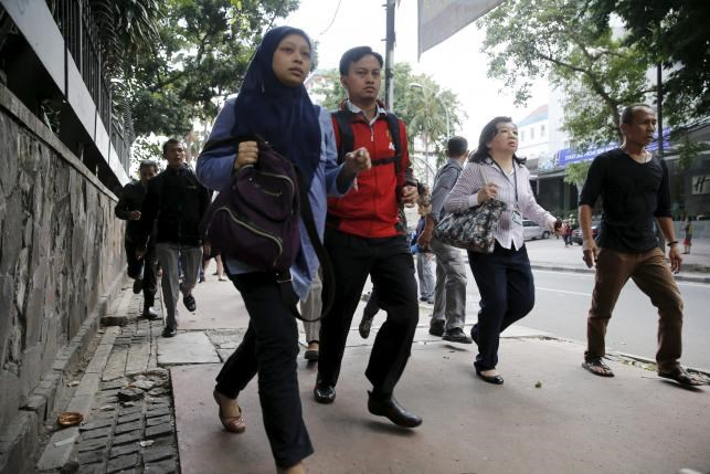 Indonesian workers run as they are evacuated from their office at Thamrin business district in Jakarta January 14, 2016.