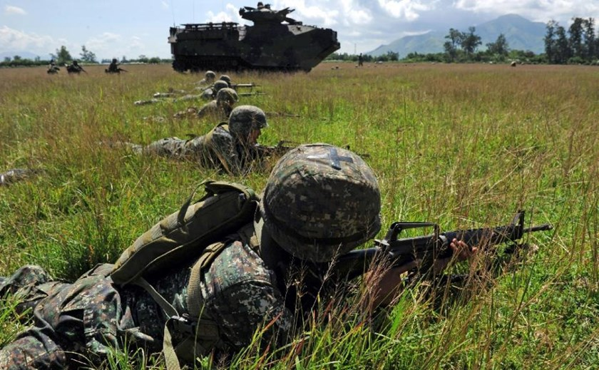 Philippine Marines take position next to a US Marine assault amphibious vehicles during a live-fire exercise at a naval training center in San Marcelino, north of Manila on October 9, 2015