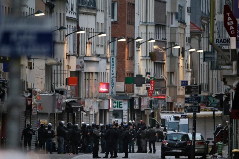 Police officers gather in the northern Paris suburb of Saint-Denis city centre on November 18, 2015, as French Police special forces raid an apartment, hunting those behind the attacks that claimed 130 lives