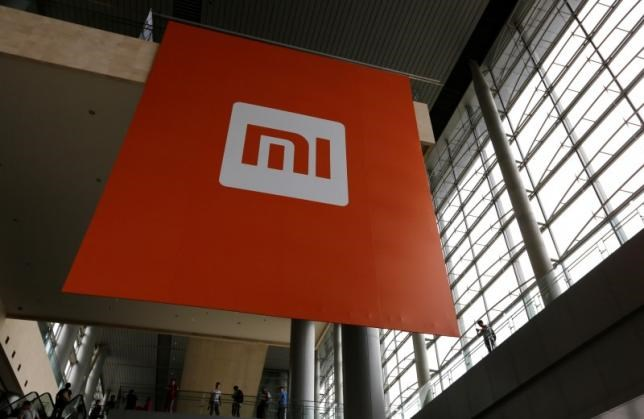 People stand near a logo of Xiaomi ahead of the launching ceremony of Xiaomi Phone 4, in Beijing, July 22, 2014. Picture taken July 22, 2014.