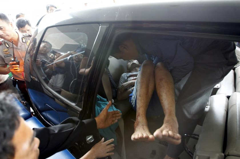 A man wounded in a gun and bomb attack in central Jakarta is helped from a car upon arrival at a hospital in Jakarta January 14, 2016.
