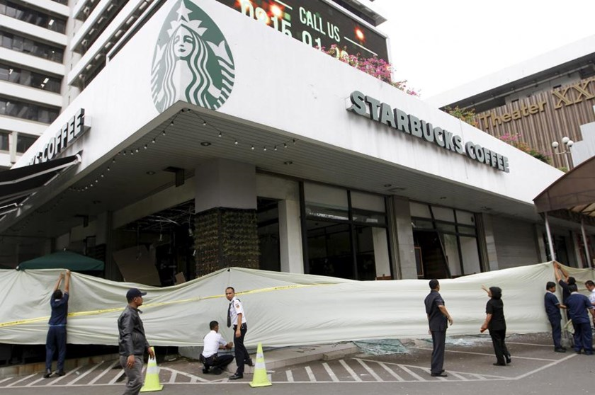 Workers set a cordon to enclose a cafe after it received damage following a gun and bomb attack in central Jakarta January 14, 2016.