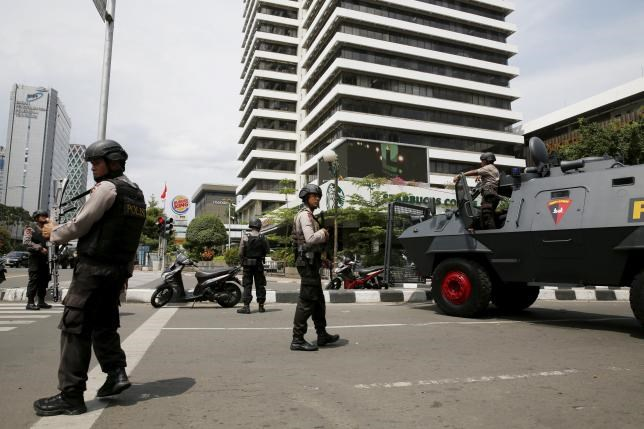 Indonesian policemen with weapons and an armoured vehicle guard in front of a Starbuck cafe at Thamrin business district in Jakarta, January 14, 2016.