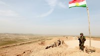 A Kurdish Peshmerga fighter takes up position with his weapon as he keeps watch, on the outskirts of Mosul January 26, 2015.