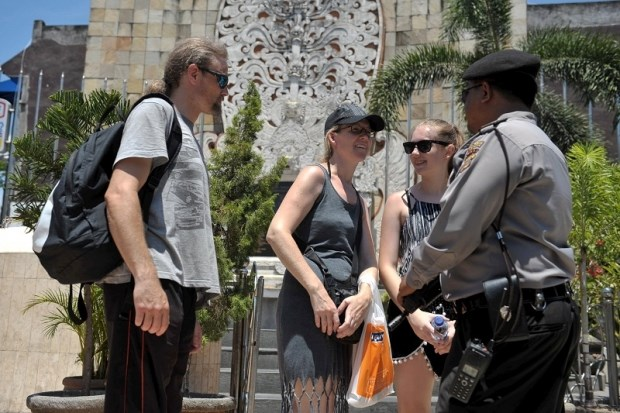 An Indonesian police officer holds a weapon as he talks with tourists in front of the Bali Bomb Monument in Kuta, Bali resort island, January 15, 2016 in this photo taken by Antara Foto. Reuters