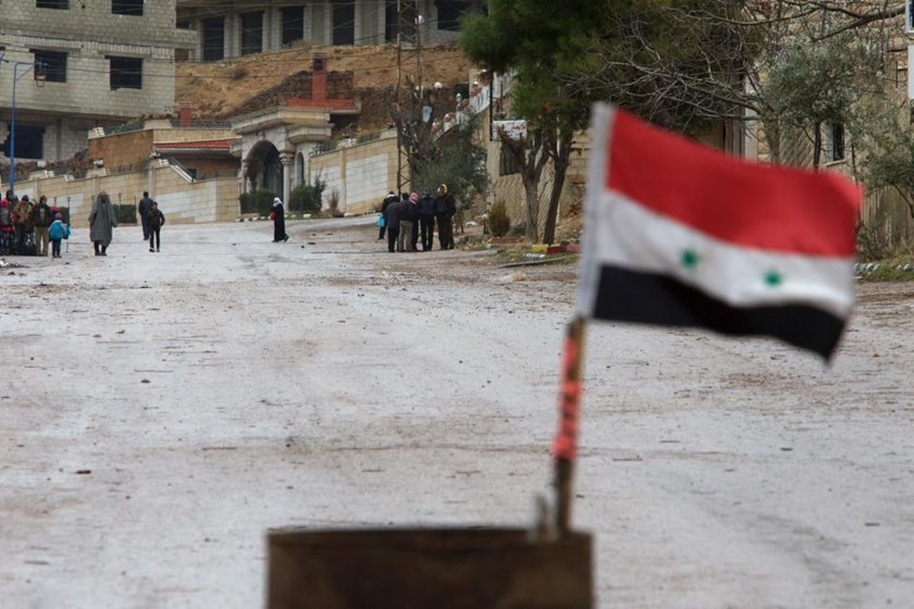 A Syrian national flag flutters near residents who said they have received permission from the Syrian government to leave the besieged town as they wait with their belongings after an aid convoy entered Madaya, Syria, January 14, 2016.