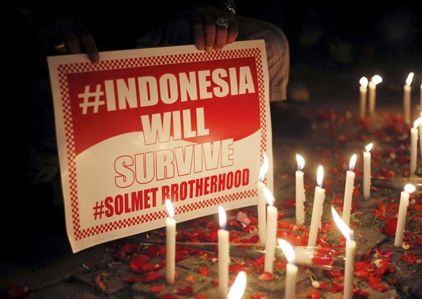 A man holds a placard during a peace gathering at the site of this week's militant attack in central Jakarta, Indonesia January 16, 2016.