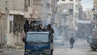 Rebels drive through the eastern Syrian town of Deir Ezzor on March 10, 2014