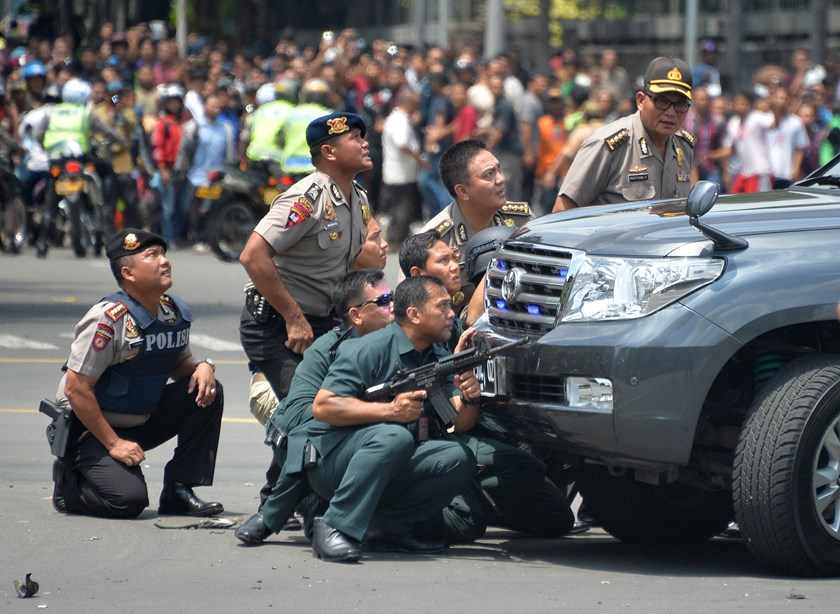 Indonesian police take position behind a vehicle as they pursue suspects after a series of blasts hit the Indonesia capital Jakarta on Thursday. Photo: AFP