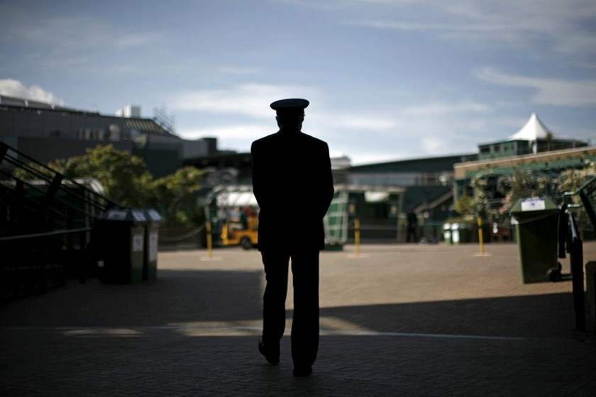 A steward walks the quiet grounds before the gates are opened to the public for the first day of play at the Wimbledon tennis championships in London in this June 23, 2008 file photo
