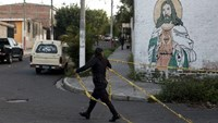 A police officer takes down a yellow police tape at a crime scene in Soyapango, on the outskirts of San Salvador September 26, 2015.