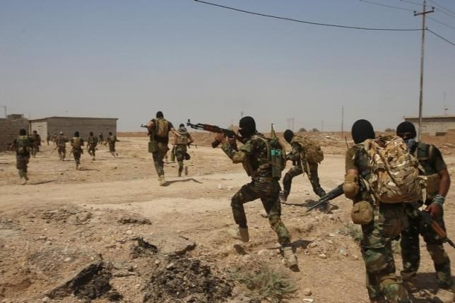 Asaib Ahl al-Haq Shi'ite militia fighters from the south of Iraq run during a mission to take control of Sulaiman Pek village from Islamist State militants, in the northwest of Tikrit city September 1, 2014.