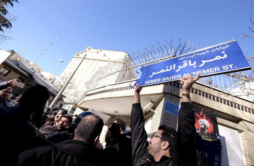 An Iranian protester holds up a street sign with the name of Shi'ite cleric Sheikh Nimr al-Nimr during a demonstration against the execution of Nimr in Saudi Arabia, outside the Saudi Arabian Embassy in Tehran January, 3, 2016.