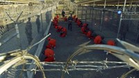 Detainees in orange jumpsuits sit in a holding area under the watchful eyes of military police during in-processing to the temporary detention facility at Camp X-Ray of Naval Base Guantanamo Bay in this January 11, 2002 file photograph.