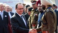 French President Francois Hollande (centre L) shakes hands with a member of the welcoming party on his arrival at the Indian military base in Chandigarh on January 24, 2016