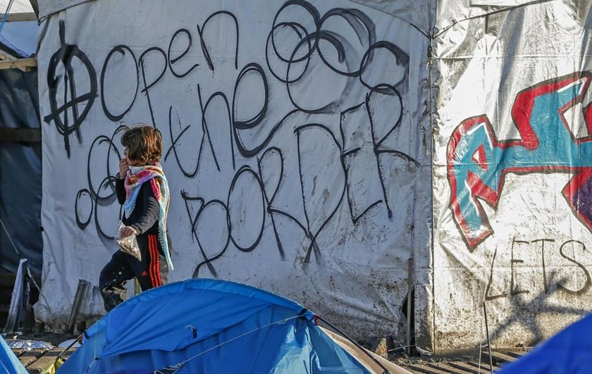 A young migrant walks past graffiti reading 'Open the border' in a muddy field at a camp of makeshift shelters for migrants and asylum-seekers from Iraq, Kurdistan, Iran and Syria, called the Grande Synthe jungle, near Dunkirk, France, January 25, 2016.