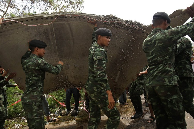 Thai soldiers carry a piece of suspected aircraft debris after it was found by fishermen on Jan. 23. Photo: AFP