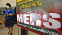 A woman wearing a mask walks past an information banner on Middle East Respiratory Syndrome (MERS) at the entrance of Bamrasnaradura Infectious Diseases Institute in Nonthaburi province, on the outskirts of Bangkok, Thailand, June 19, 2015.